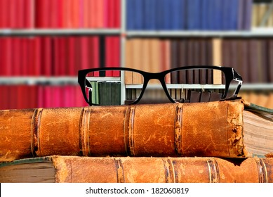 Old books and eye glasses with sharp vision through them on the books against the indistinct (unsharp, not in focus) background - Concept of visual acuity return