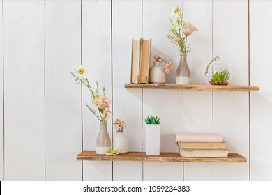 Old books and flowers in a vase on a wooden shelf, frame with flowers on a wooden wall. Wooden shelves with books and flowers on the wall