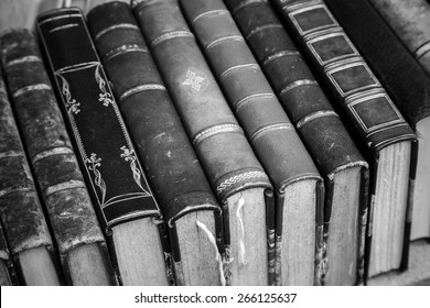Old books with leather covers lay on the shelf, vintage stylized monochrome photo