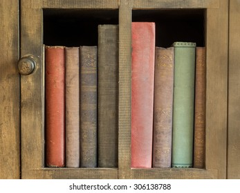 old books lined up in an antique bookcase