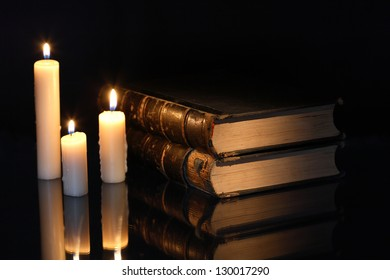 Old books near lighting candles on dark background