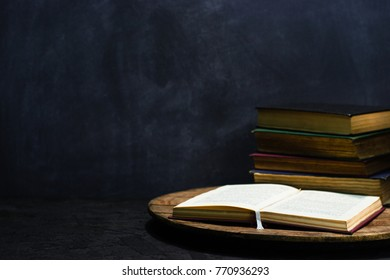 Old books on a round wooden table. Beautiful dark background.