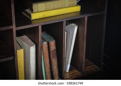 Old books on a shelf in different positions