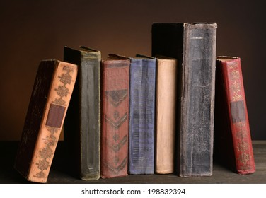 Old books on table on brown background