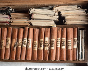 Old books on wooden bookshelf. Brown books standing in a row on wooden shelf. Vintage shabby books on bookrack, background. Image of the bookcase with ancient writing
