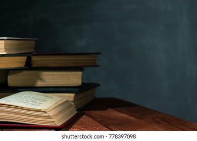 Old books on a wooden red table. Beautiful dark background.