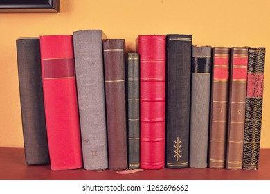 Old books on wooden shelf. Antique books on yellow and claret background.