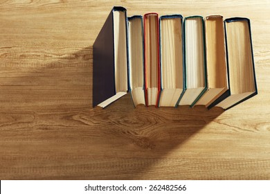 Old books on wooden table, top view