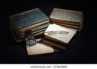 old books, papers, ink pen and inkpot on black background