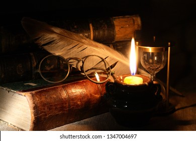 Old books and quill pen near lighting candle on dark background