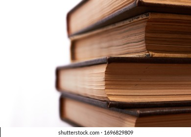 Old books stacked in column. Years of wisdom embodied in encyclopedias that today are overtaken by technology and the internet. Wood symbolizes years gone by and old age.
