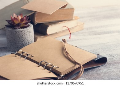 Old books, succulent and open craft notebook on rustic wooden background. Office desk table - Shutterstock ID 1170670951