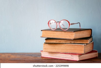 Old books with vintage glasses on a wooden table. retro filtered image