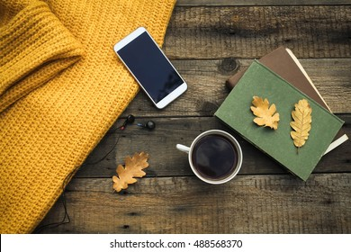 Old book,smart phone , autumn leaves  on wooden background. Concept autumn. Top view