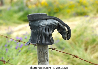 Old boot broken on the fence wire at the edge of pilgrim path
