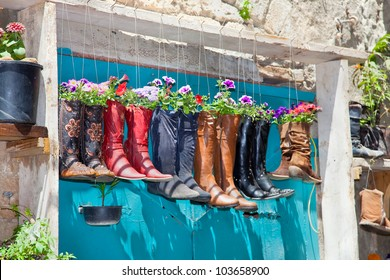 Old boots used as flower pots on the entrance door of a house, Israel
