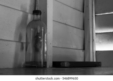 Old bottle on wooden shelf in black and white tone.