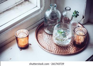 Old bottles, candles on a copper vintage tray, vintage home decor