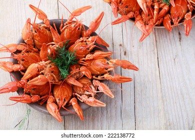 Old bowl with red boiled crawfish on a wooden table in rustic style, close-up, selective focus on some crawfishes