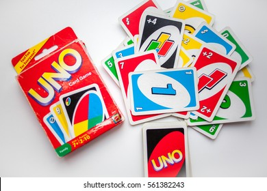 Old box of Uno card game and cards on white background