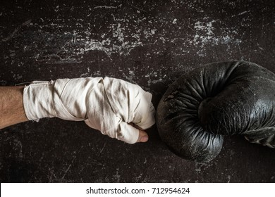 Old boxing glove against the boxing wraps is ready for fight. Dark background. Professional champion fight concept. Vintage retro style. Man's strength.