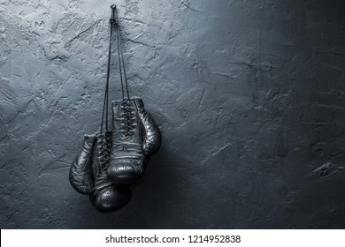 old boxing gloves hang on nail on textured wall