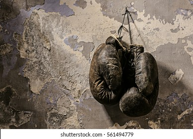 old boxing gloves hang on nail on texture wall