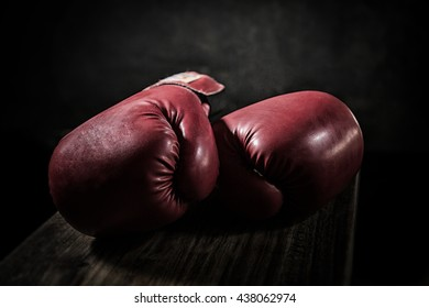 Old boxing gloves lay on the wooden floor. The concept of retirement
