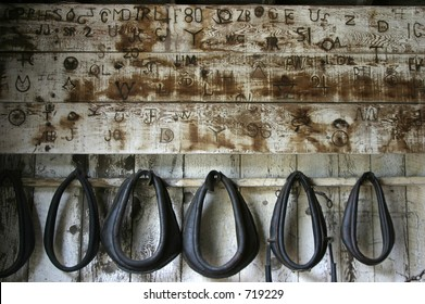 Old branding iron marks, burned onto the wall of a horse stable.
