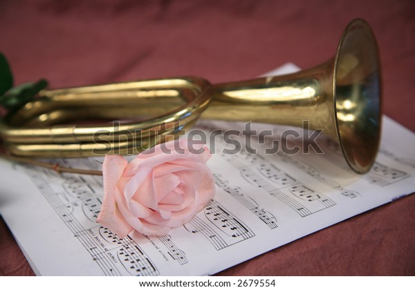 Old brass bugle pink rose and sheet music