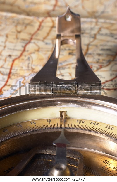 An old brass compass resting on a map.