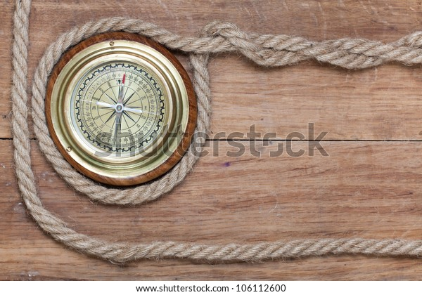 Old brass compass and rope on wood