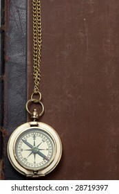 old brass compass with rusted antique book with leather back on the background
