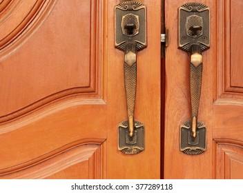 Old brass handle on wood door.