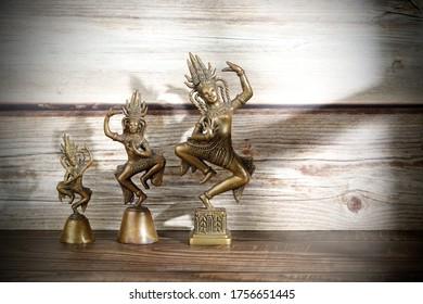 Old brass idol on wood background