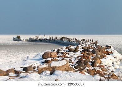 Old breakwater in frozen gulf of Riga, Baltic sea.