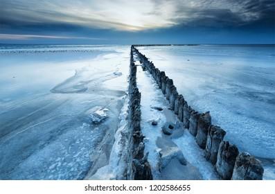 old breakwater frozen in winter by coast