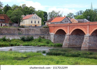 Old brick bridge over river Venta in Kuldīga, Latvia with old houses in the background.