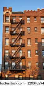 Old brick building with fire escapes at sunset, New York City, USA.