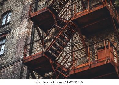 Old brick building, metal emergency stairs on building facade