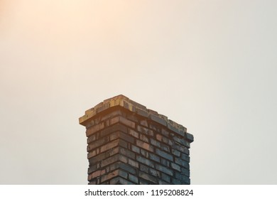 Old brick chimney on the roof, against the blue sky, smoke from the chimney