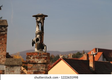 Old brick chimney on the roof with the sky in the background.