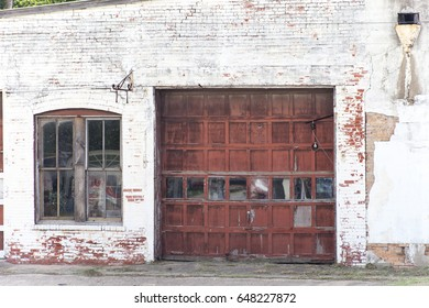 Old brick garage with a weathered  red door and window