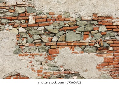 An old brick and stone wall with crumbling plaster