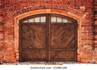 Old Brick Wall with Arch and Wooden Door.