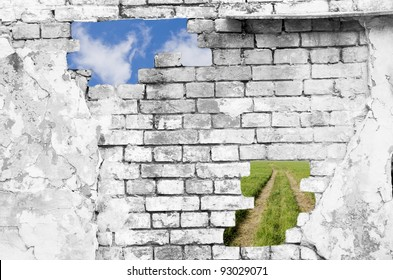 Old brick wall in black and white (with blue sky and lane across a green field showing through the holes)
