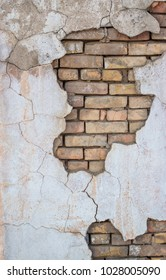 old brick wall with crumbled plaster
