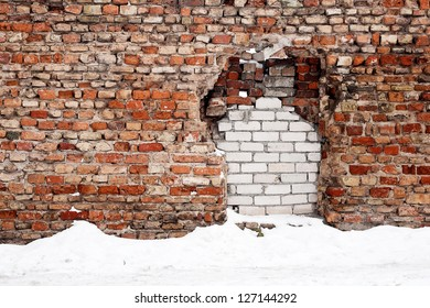 Old brick wall with immured gap in winter