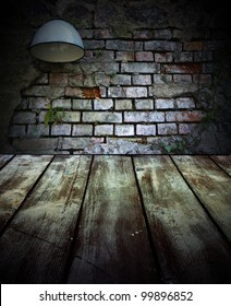 Old brick wall with a lamp and wooden floors.