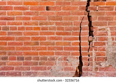 An old brick wall with major cracks and structural damage.